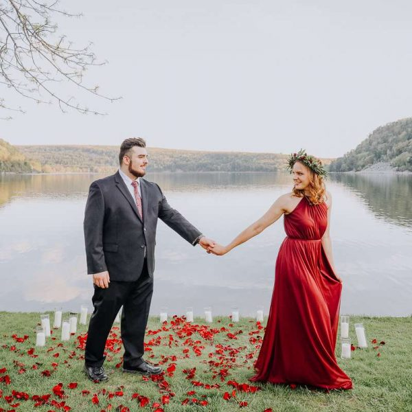couple pose on lake standing on red petals
