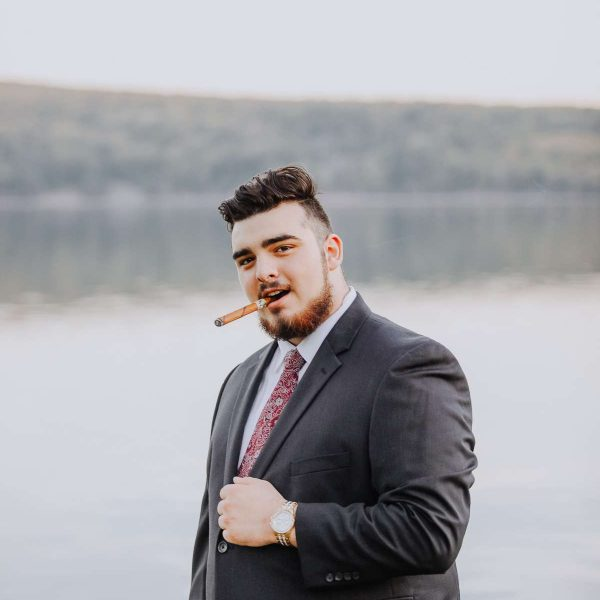 man in suite with cigar in mouth by lake