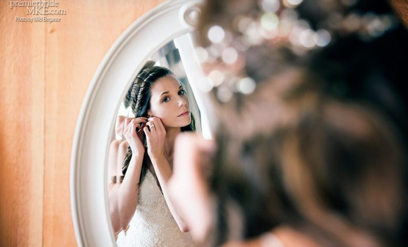 bride looking in mirror puttin on earrings