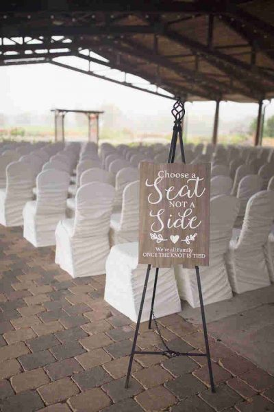 Outdoor ceremony with chairs covered with white covers at Hawk's View Golf Club
