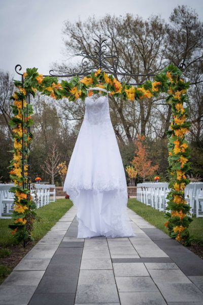 Wedding gown hung on floral draped arch