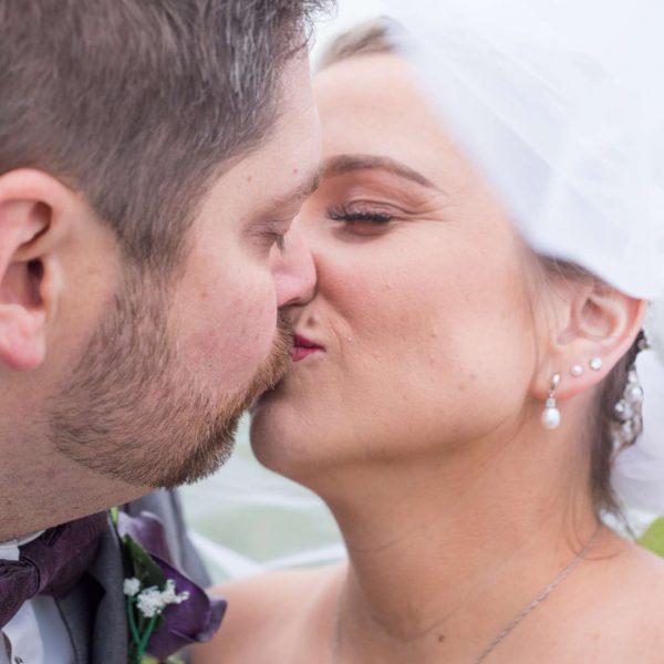 Close up of Groom kissing bride under veil