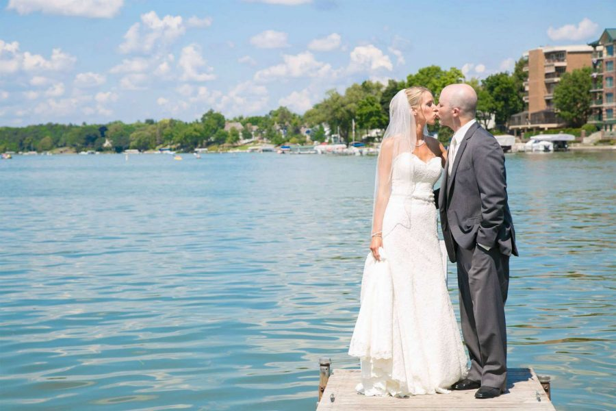 Bride & groom kiss on pier at Oconomowoc Community Center