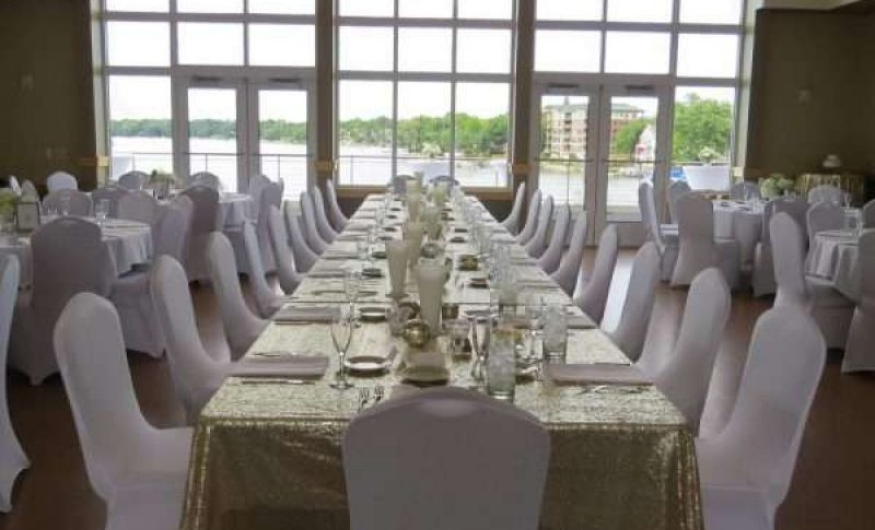 Wedding reception table with large windows in background overlooking Lac La Belle
