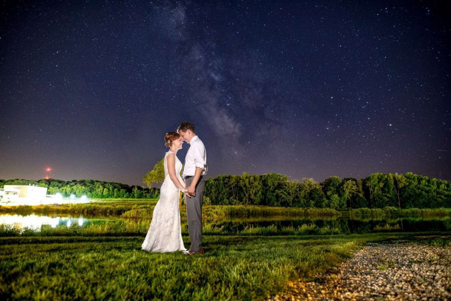 Bride and groom holds hands under the stars