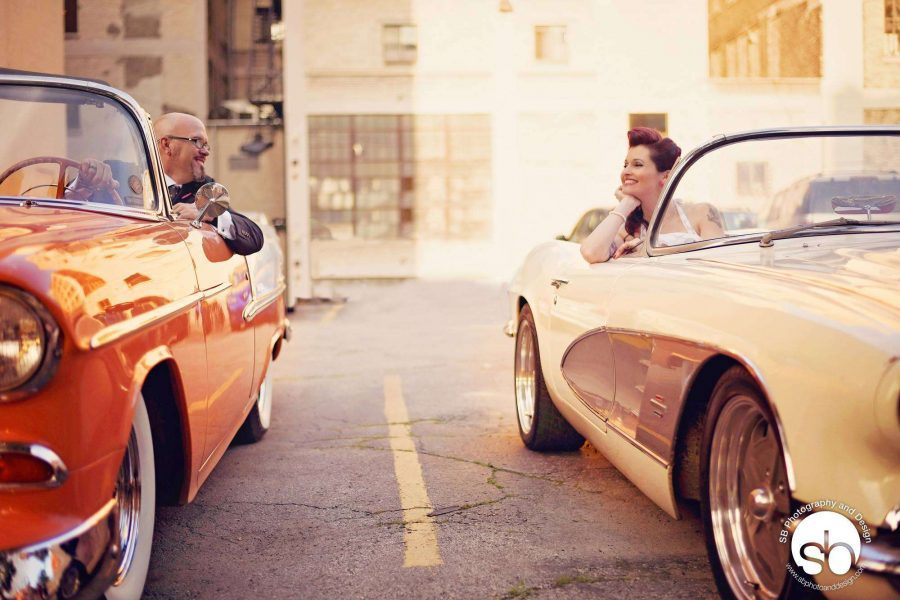 Bride and groom both in classic cars gaze at each other
