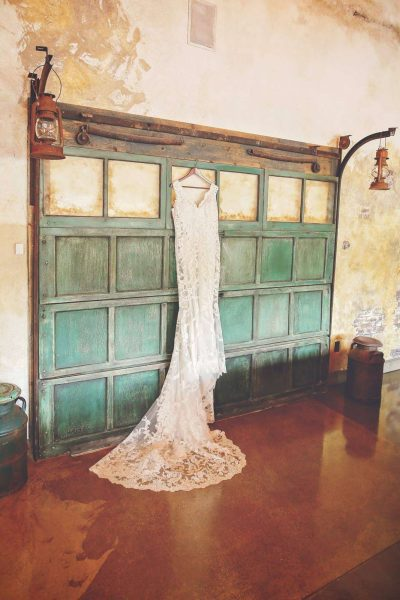 wedding gown hanging on green garage door