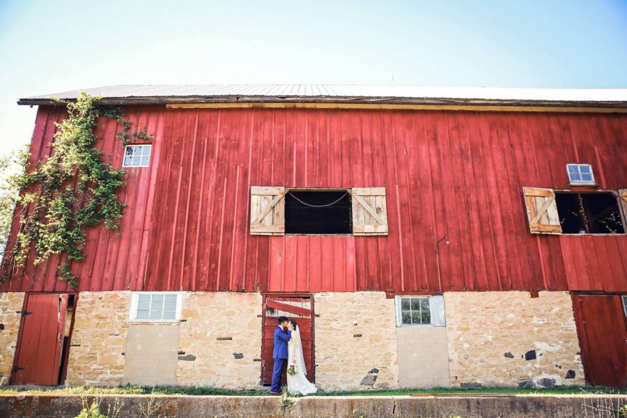 Bride & Groom kiss near a vintage red barn