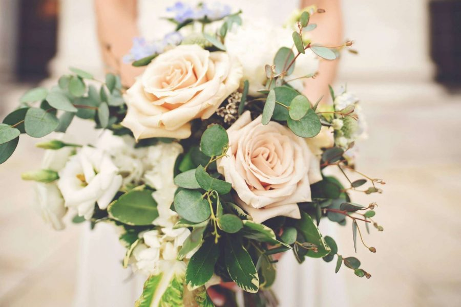 Beautiful bridal bouquet of cream roses and greenery