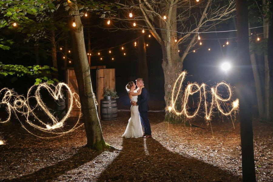 bride and groom embrace with love sparklers illuminate the word LOVE
