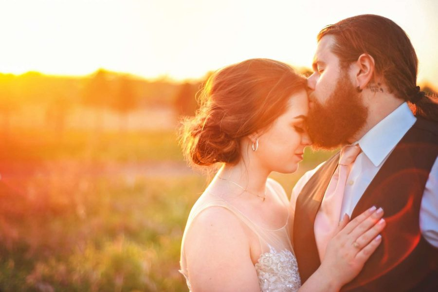 groom kisses bride forehead in the sunset