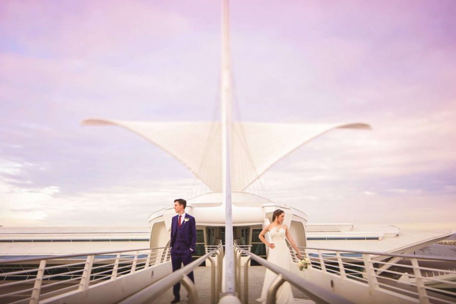 Bride and groom pose in from of the entrance to the Milwaukee Art Museum