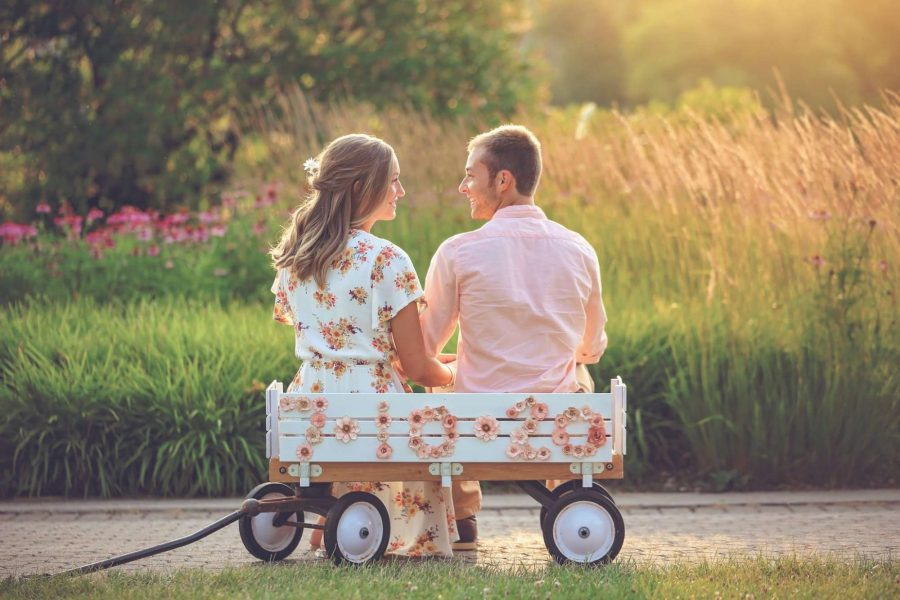 Engagement photo with couple in wagon with wedding date on it