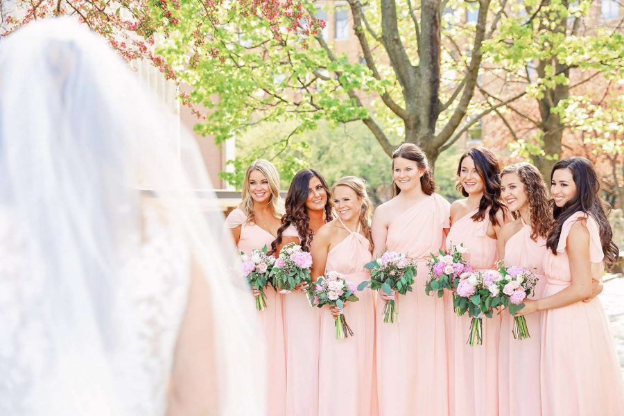 bridesmaids in pale pink look at bride