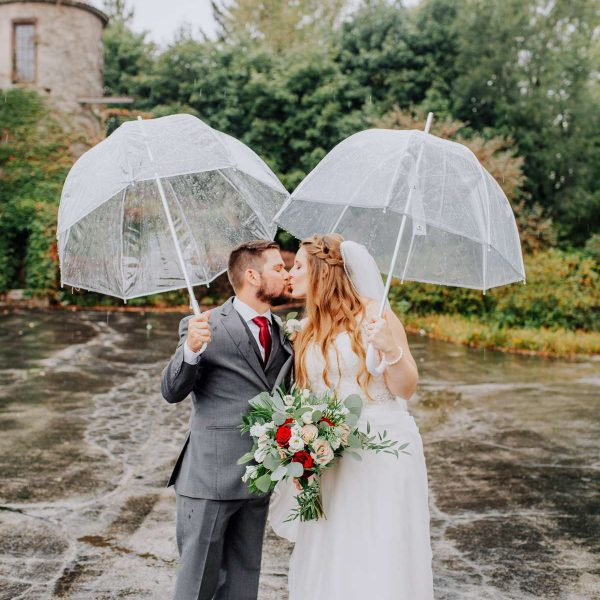 Couple kiss in the rain with their umbrellas