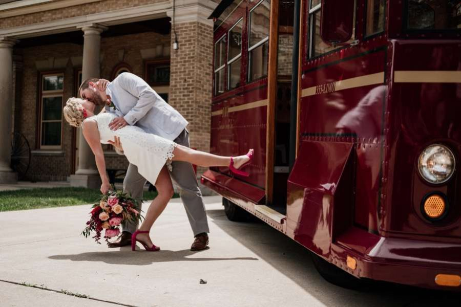 Groom dips bride and kisses her at Story Hill Firehouse