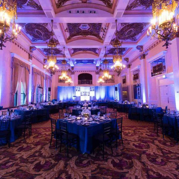 Purple up-lighting showcasing fully decorated Grand Ballroom from dramatic ceiling to tables