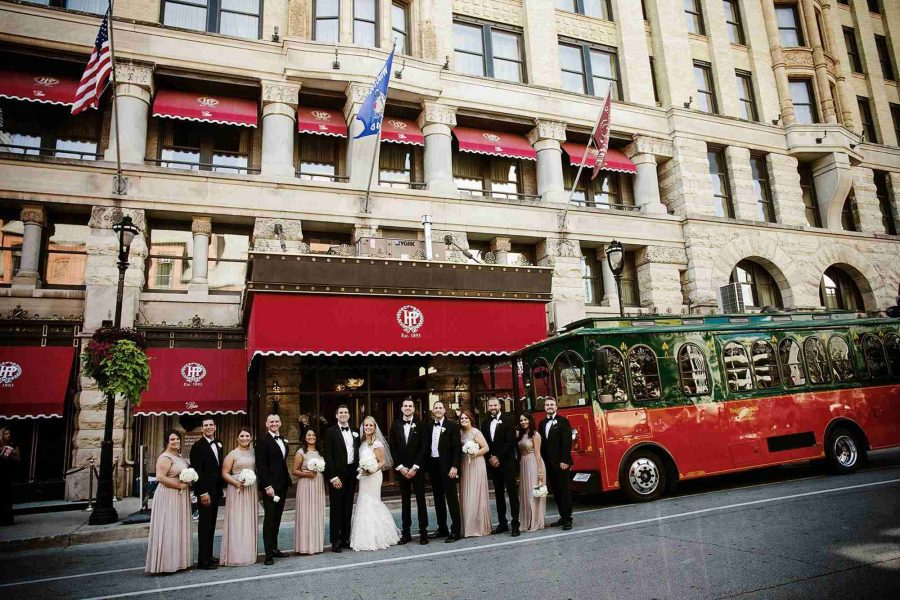 wedding party poses outside of the historic Pfister Hotel in Milwaukee, WI | Ideal Impressions Photography with Trolley