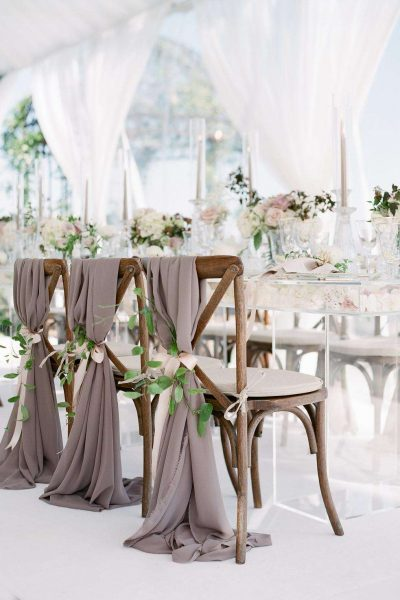 Rustic X-back farm house chairs with sash tied with fresh flowers set up with elegant white tablescape