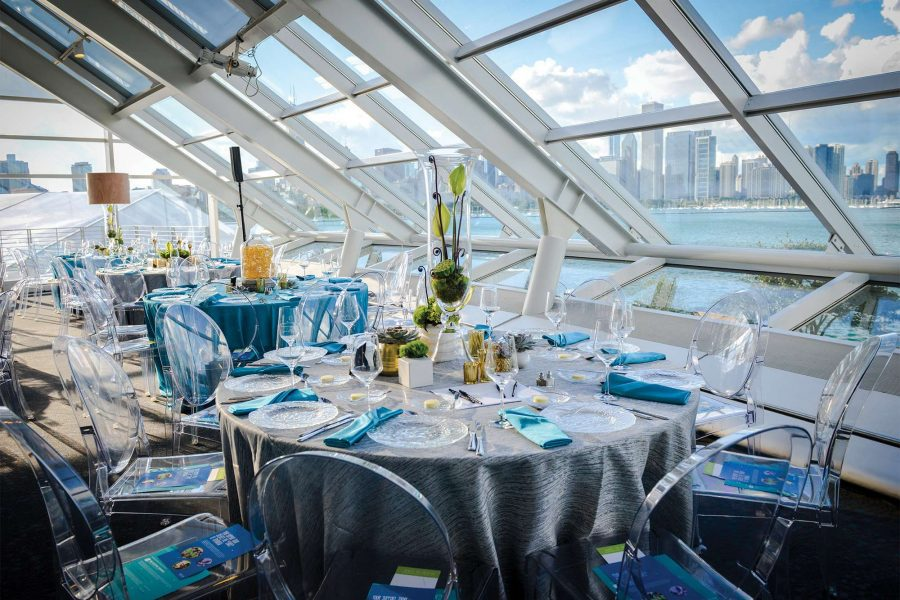 Modern wedding reception decor with mirage chairs and gray table linens with turquoise napkins by Well Dressed Tables