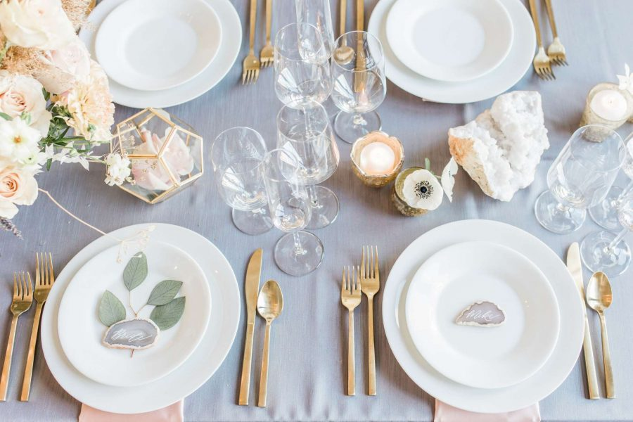 Simple and elegant place setting with white china and gold Titan Arezzo flatware atop gray table linen