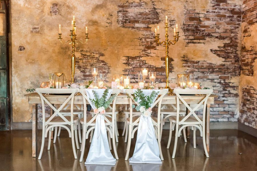 Stylish gold décor with ivory linens, royal gold flatware, and elegant white china on a gold chargers provided by Well Dressed Tables