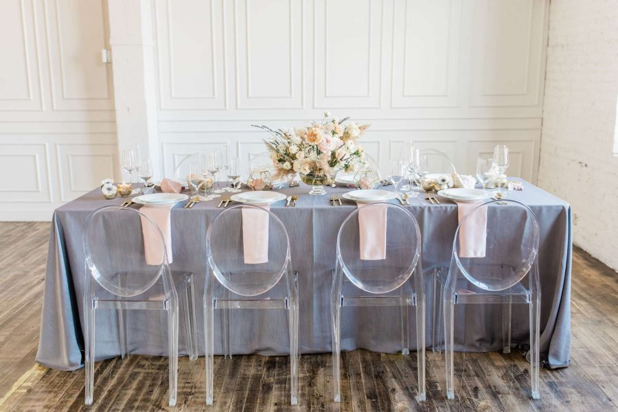 Mirage chairs at an elegant wedding tablescape with pewter linens and light pink napkins by Well Dressed Tables