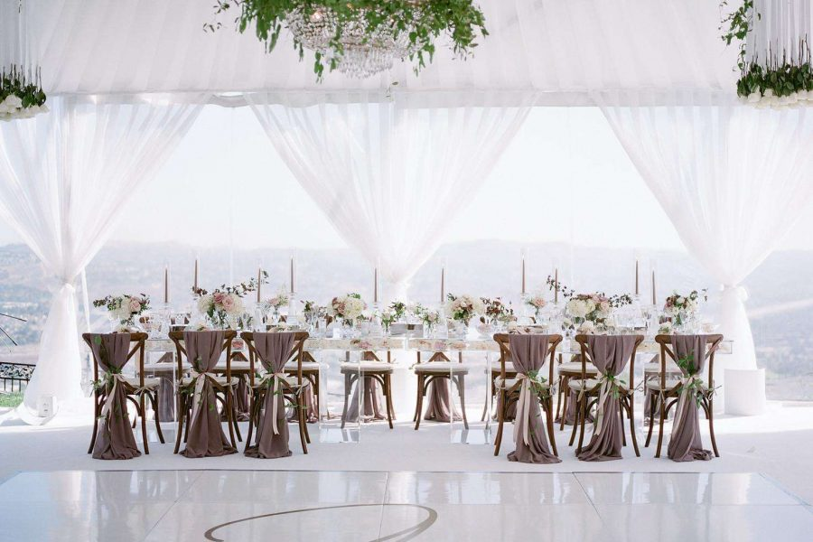 Elegant white pipe and draping are background for highboy tables and farmhouse chairs