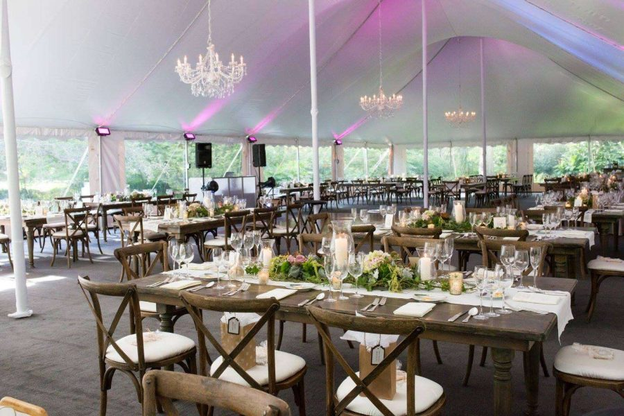 Tented wedding reception with farm tables and chairs provided by Well Dressed Tables