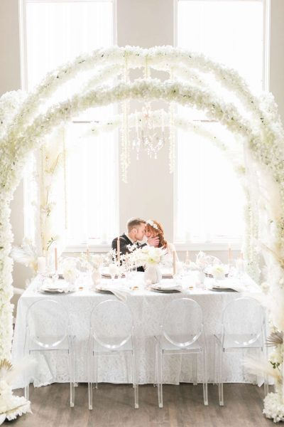 Bride and groom sit at square kings table with mirage chairs and elegant white floral canopy