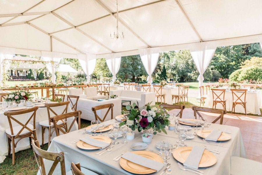 Tent wedding reception with square tables, white linens, and farm house cross backed chairs by Well Dressed Tables
