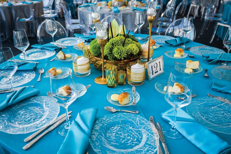 Round table with Turquoise Matte Satin table linens set with transparent plates by Well Dressed Tables