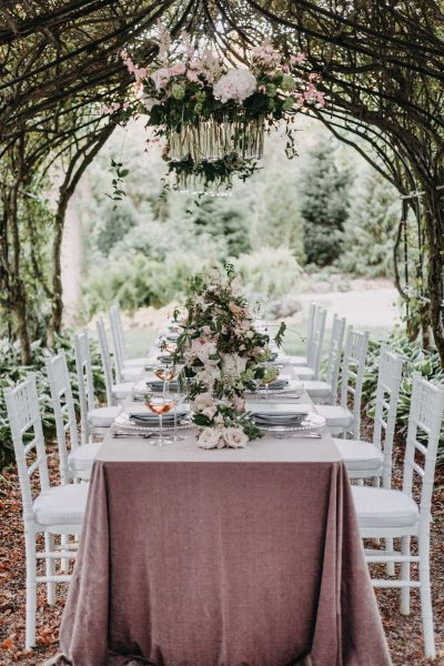 Long rectangular table with dusty rose linens and white chiavari chairs