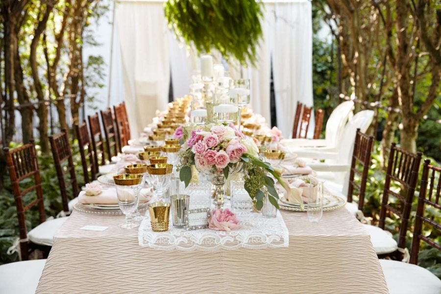 Outdoor wedding table setting with chiavari chairs and gold rimmed glassware