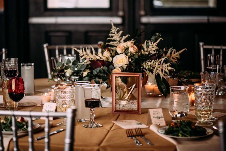 Tablescape with silver chiavari chairs and rust colored linens. A mirror with number painted on is used for the table number.