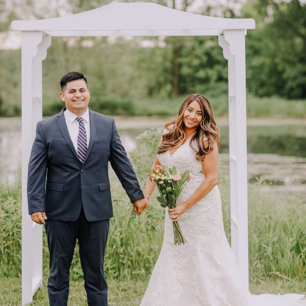 Wedding couple pose hand in hand by white arch