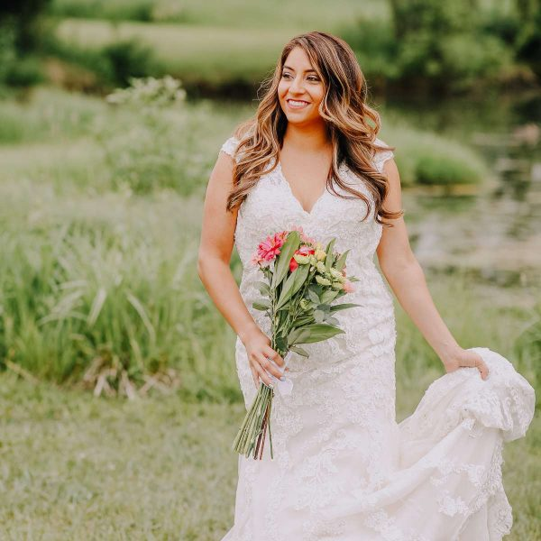 Bride walking in meadow with her bouquet in hand