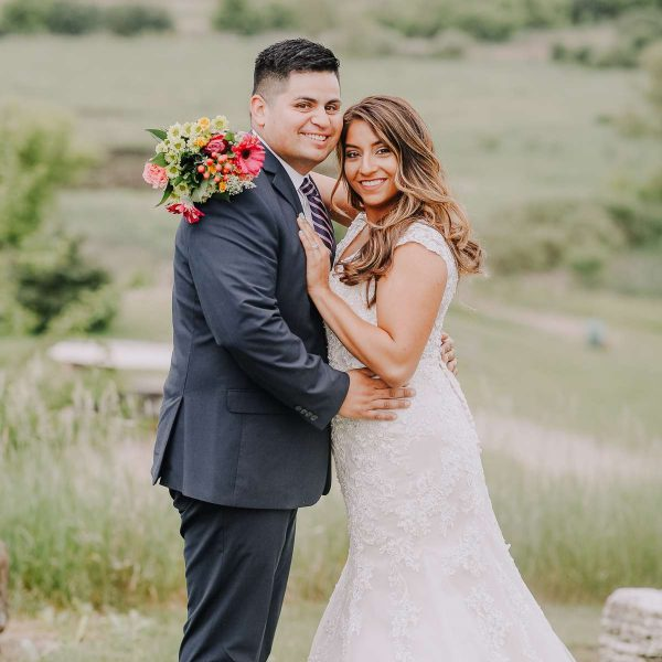 Bride and groom pose on green hilltop