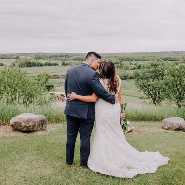 Groom & bride stand with arms around each other waist looking at meadow