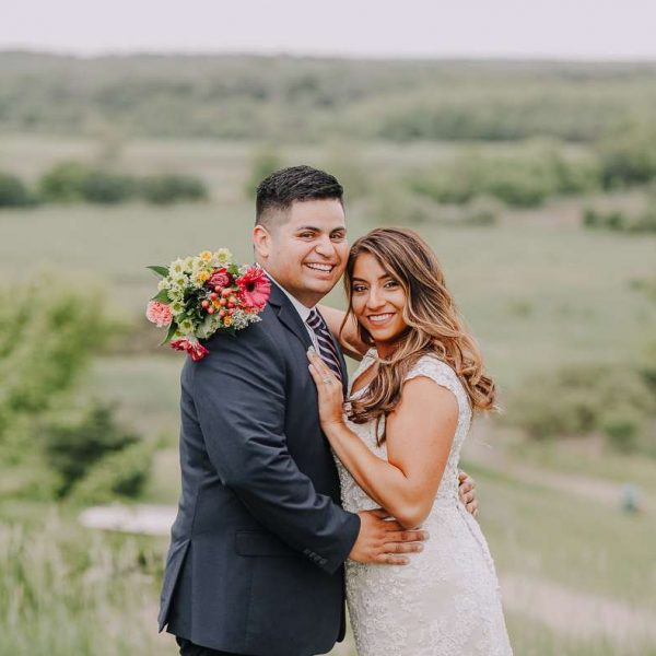 Bride and groom embrace on top of hill with bouquet
