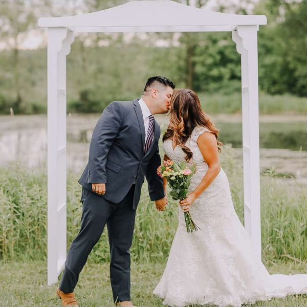 Bride and groom kiss under white wedding arch
