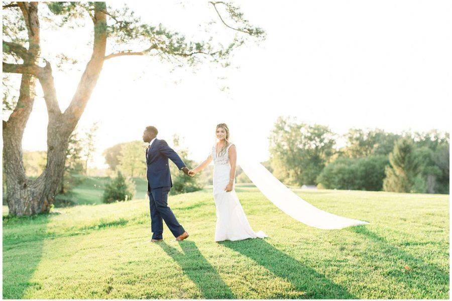 Bride and groom walk hand in hand in Oconomowoc