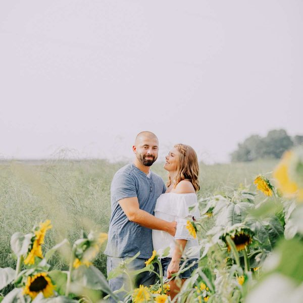 couple pose in sunflower field