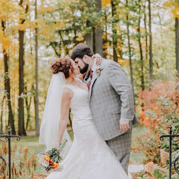 Bride and groom kiss outdoors on a fall day