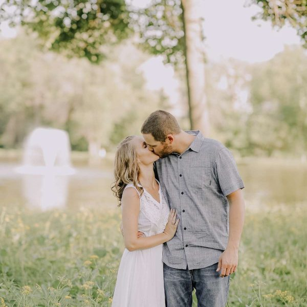 couple kissing by pond