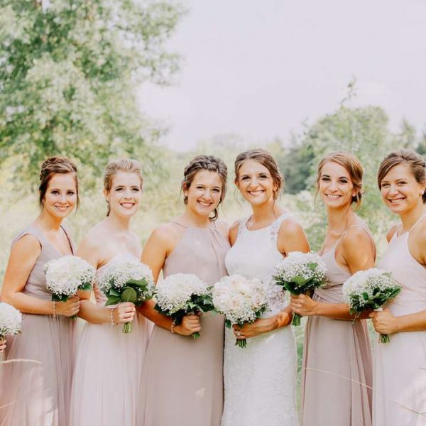 Bride and bridesmaids pose with bouquets- Summer wedding