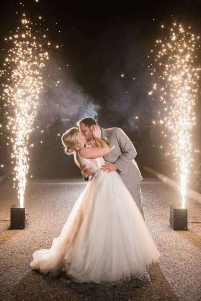 Bride and groom kiss with light sparklers in background