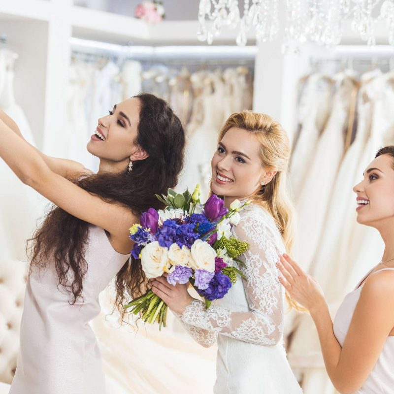 bride shopping with bridesmaids for wedding gown