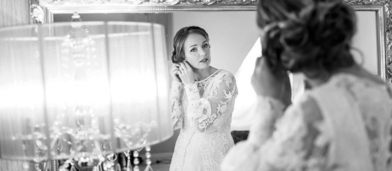 black and white photo, bride getting ready, bride looking in mirror putting on earrings