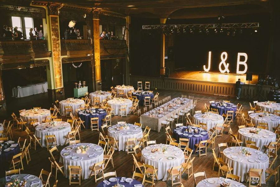 Image taken from second floor looking down over stunning wedding reception. White and purple table linen with lighted stage and large framed initials.
